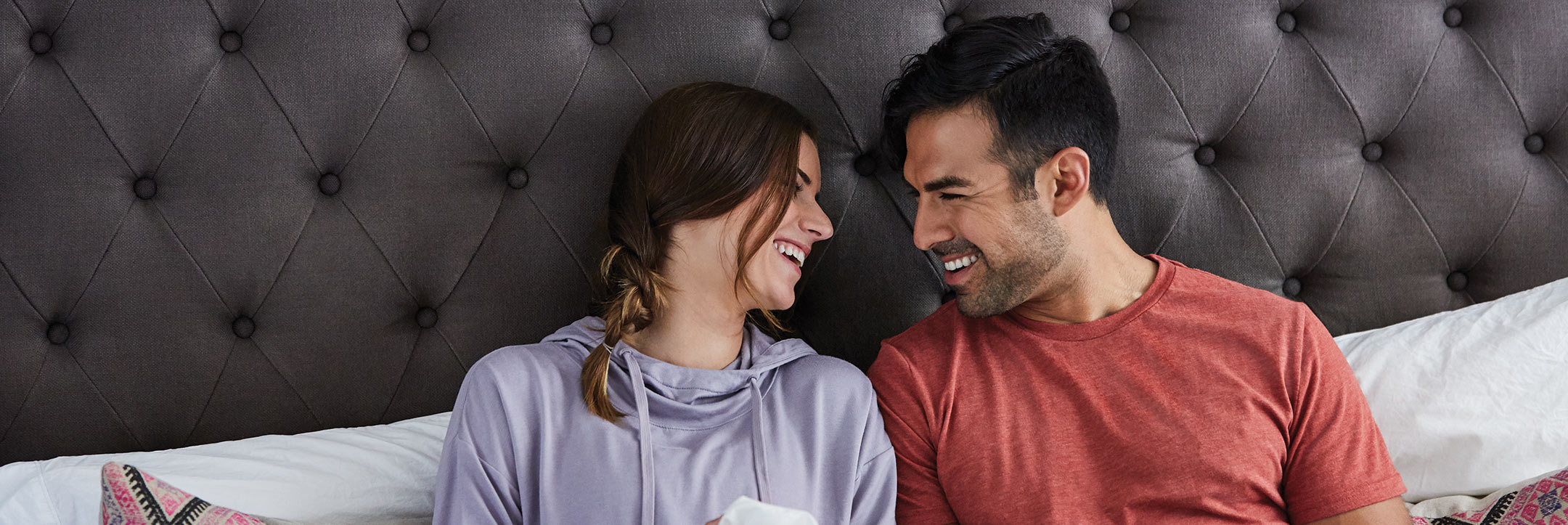 young couple laughing in bed